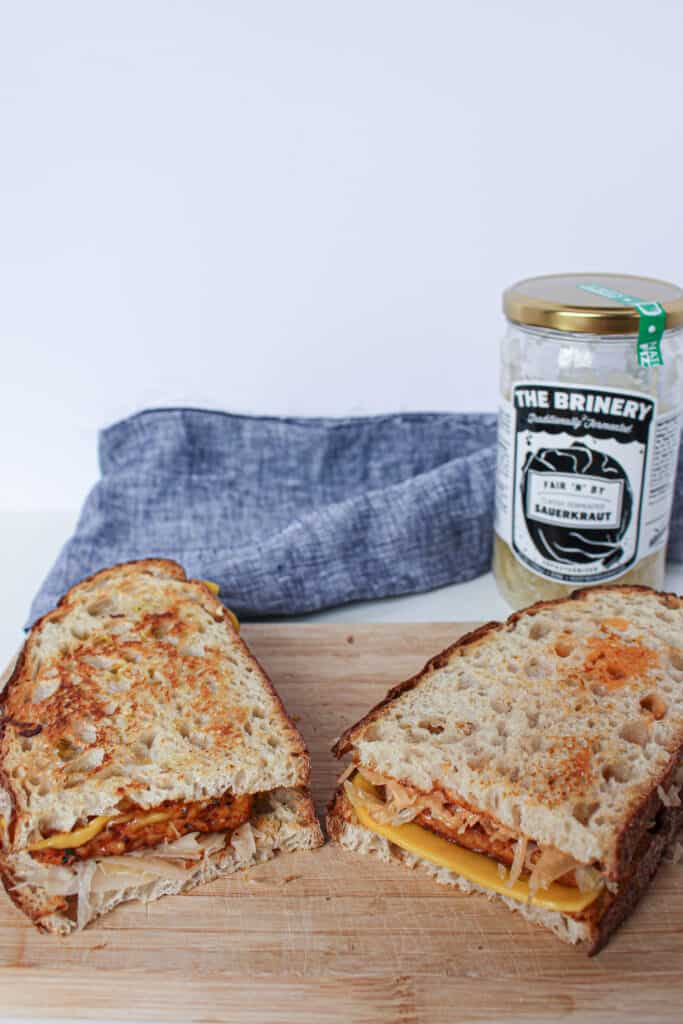 A delicious vegan tempeh reuben sandwich served on a wooden cutting board with a jar of sauerkraut in the background