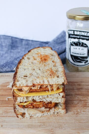 Vegan tempeh reuben sandwich with sauerkraut served on a wooden cutting board with a jar of sauerkraut in the background