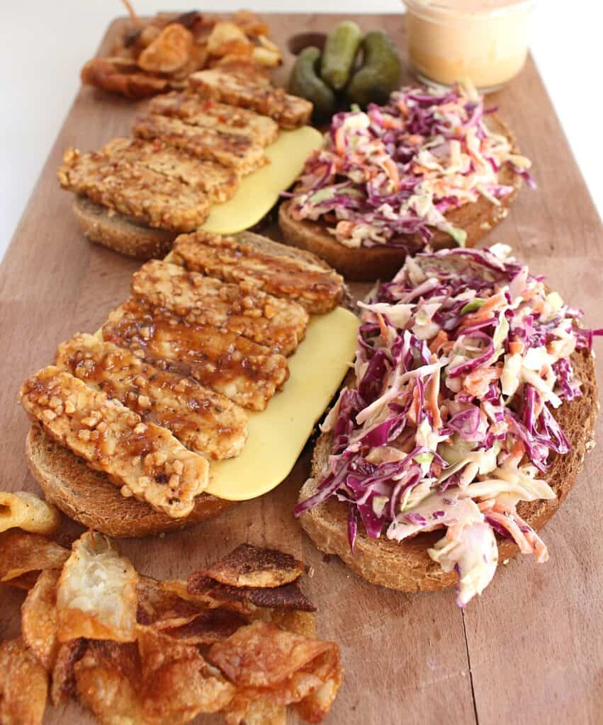 An open face tempeh reuben sandwich with coleslaw served on a wooden cutting board with chips and pickles