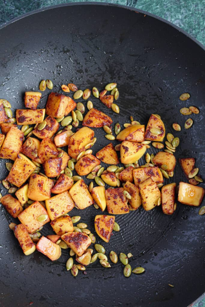Sauteed apples and toasted pepitas (a.k.a. pumpkin seeds) in a wok