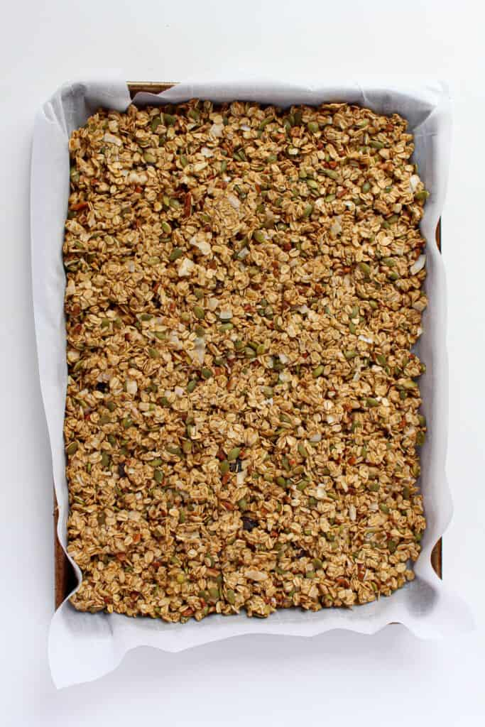 Pre-baked granola ingredients pressed down firmly on a large baking sheet that is lined with parchment paper