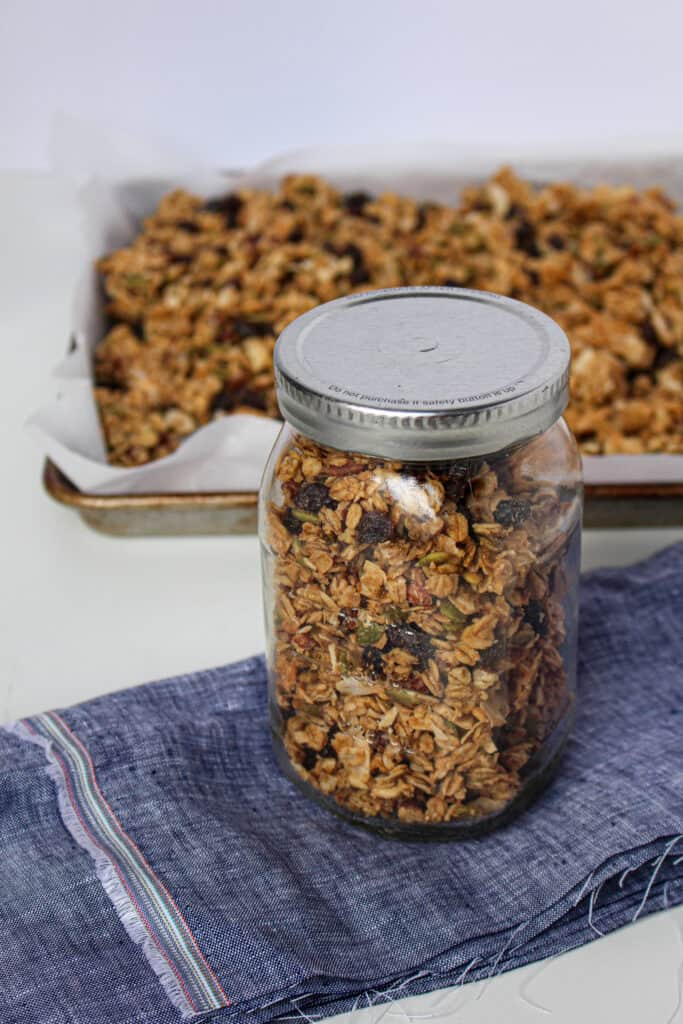 Jar of peanut butter granola in front of a baking sheet with granola on it.