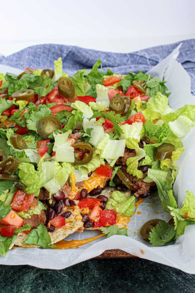Nachos on sheet pan: melty cheese over beans on chips. Topped to lettuce cilantro, tomato and pickle jalapeno