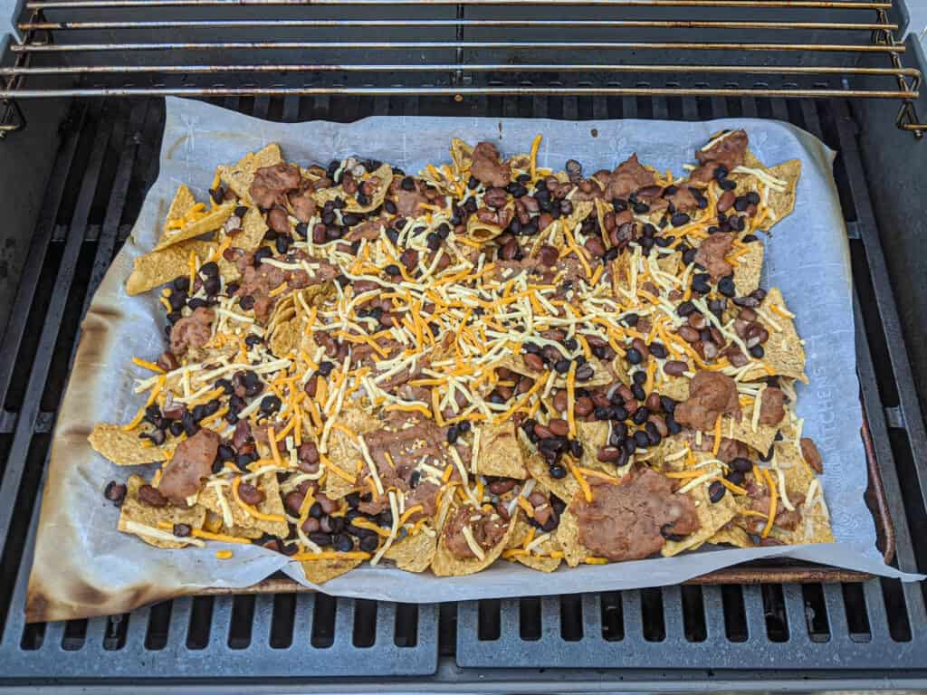 A sheet pan of nachos on the grill. Tortilla chips, black beans, refried beans with shredded Daiya cheese on a baking sheet lined with parchment paper