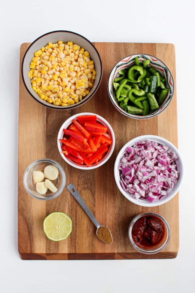 Over head view of individual ingredients on wood cutting board. 1 tsp of cumin, garlic clove in glass jar, adobe peppers in glass jar, 1/2 of lime, chopped red onion in white bowl, sliced red and green pepper in separate bowls, and frozen corn in a gray bowl