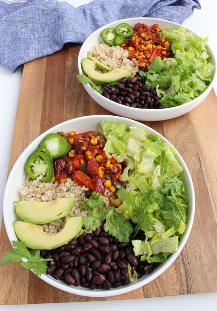 Two vegan black bean burrito bowls: white bowls filled with rice, black beans, fiesta vegetables, lettuce, cilantro and pickled jalapeno on a wooden background