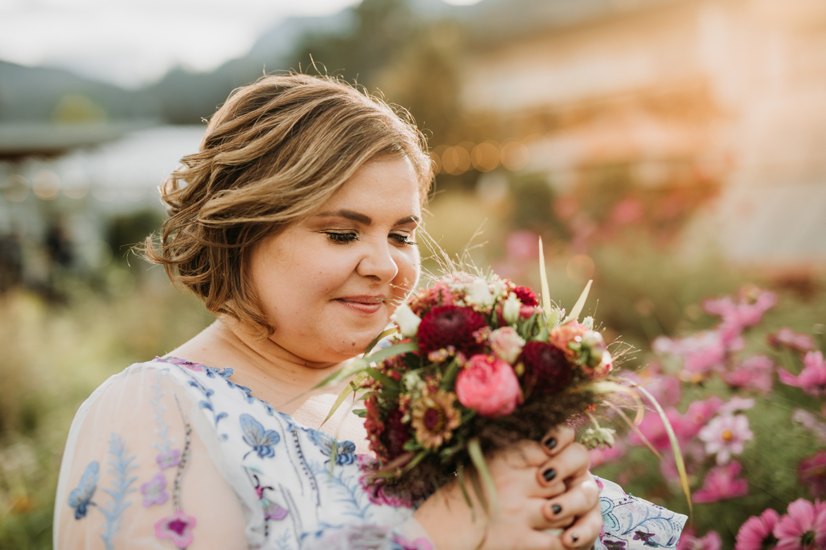 A bride is smelling her bouquet with closed eyes