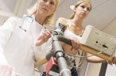 Patient in action of completing a stress test with the help of a technologist.