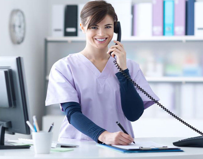 Medical receptionist in the process of booking a patient appointment over the phone.