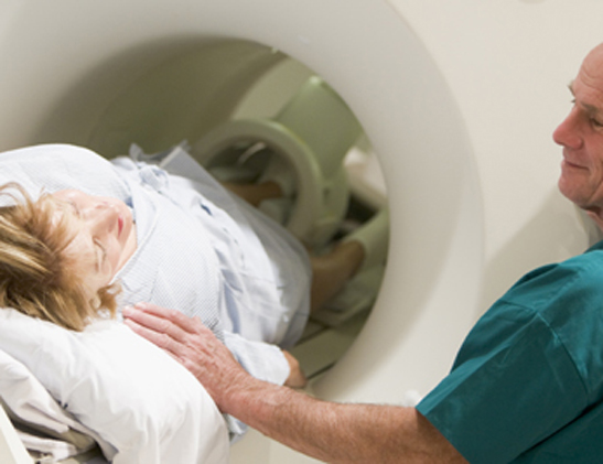 Patient preparing for a CAT scan with the help of a technologist.
