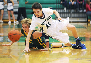 Glacier's Dylan Ruggles (21) and Whitefish's Cody Olson dive for a loose ball during the final minutes of a December 20, 2014 basketball game at Glacier High School. (Aaric Bryan/Daily Inter Lake)