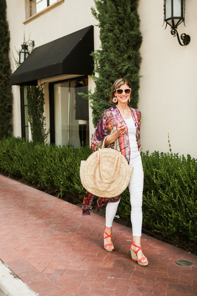 Dallas wardrobe consultant and over 50 blogger wearing Elizabeth Gillett kimono and orange wedge with pink sunnies and straw bag.