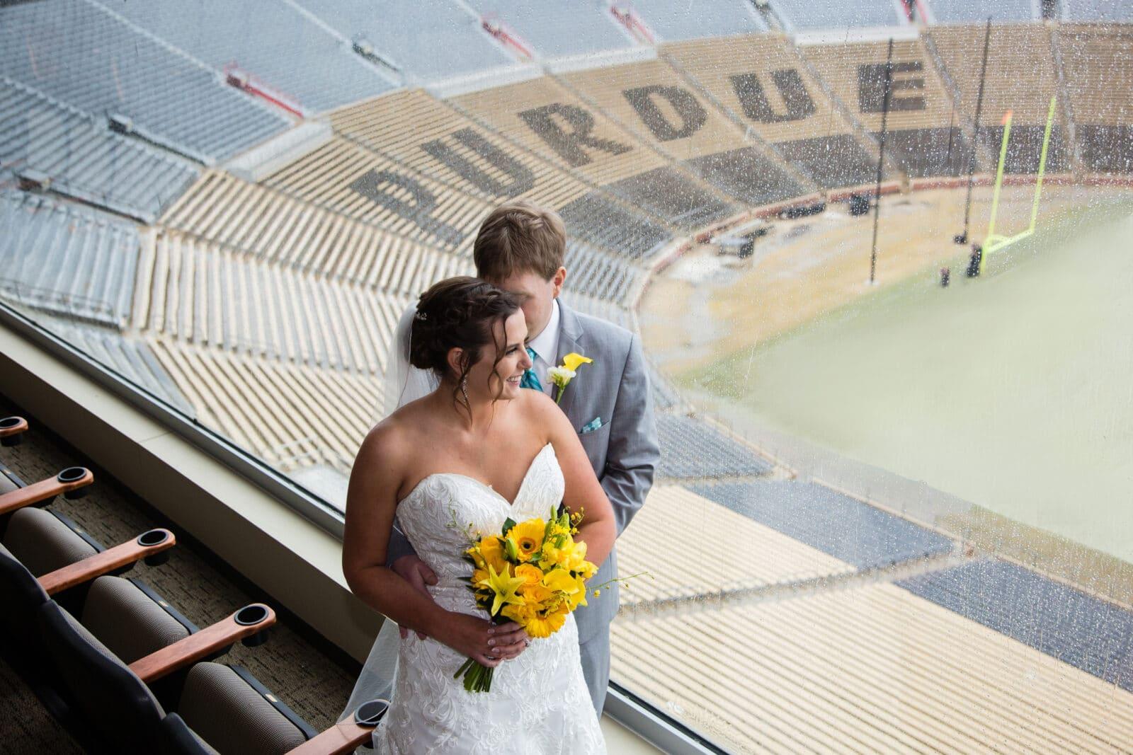 bride and groom pose at purdue university ross ade stadium