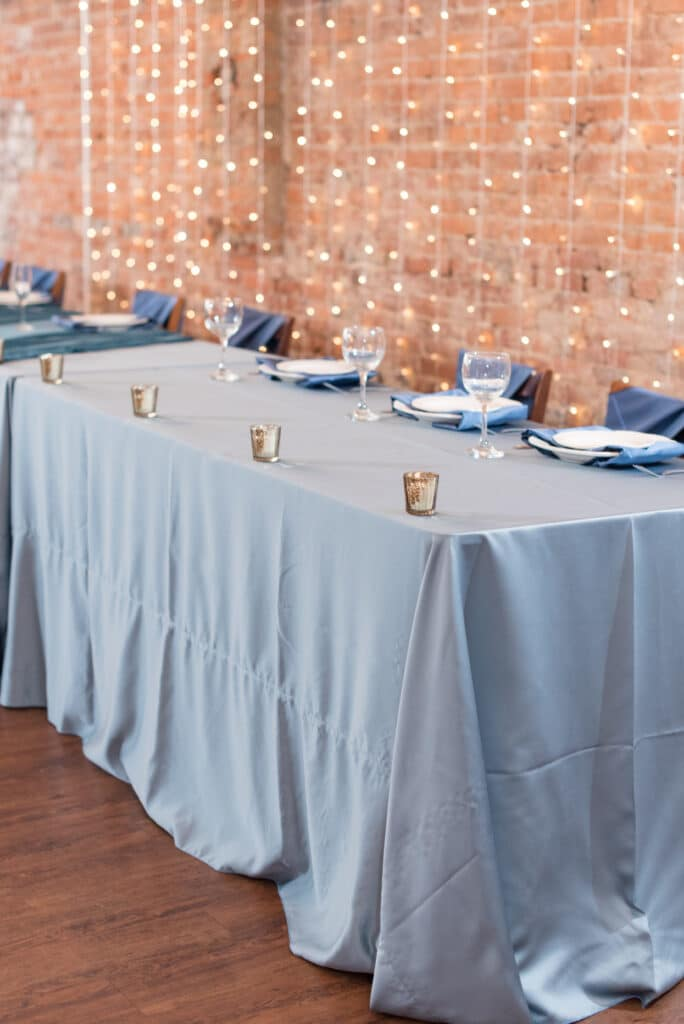 head table with slate blue linens in front of exposed brick wall