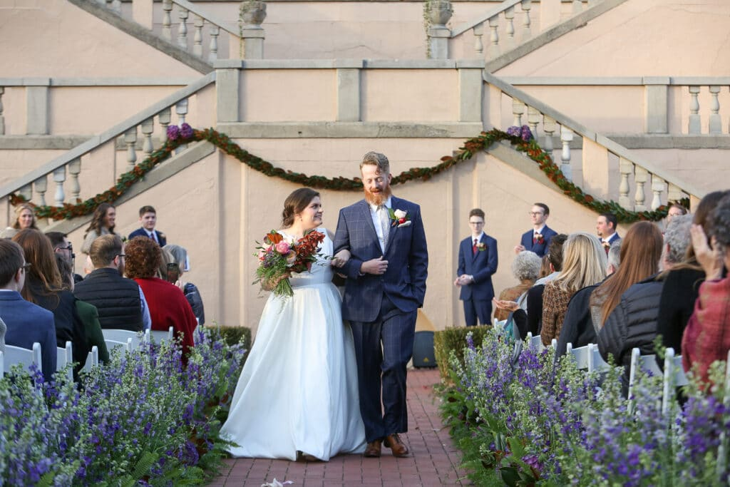 bride and groom walk down a flower-lined aisle at outdoor ceremony at fowler house mansion in lafayette, indiana