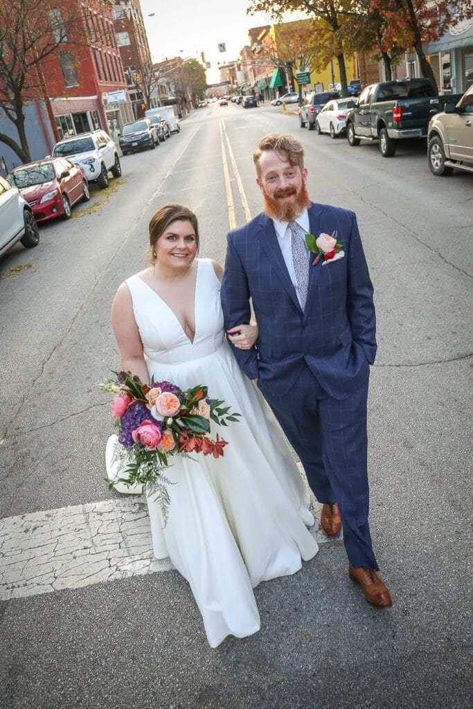 bride and groom pose in middle of the street in downtown lafayette, indiana