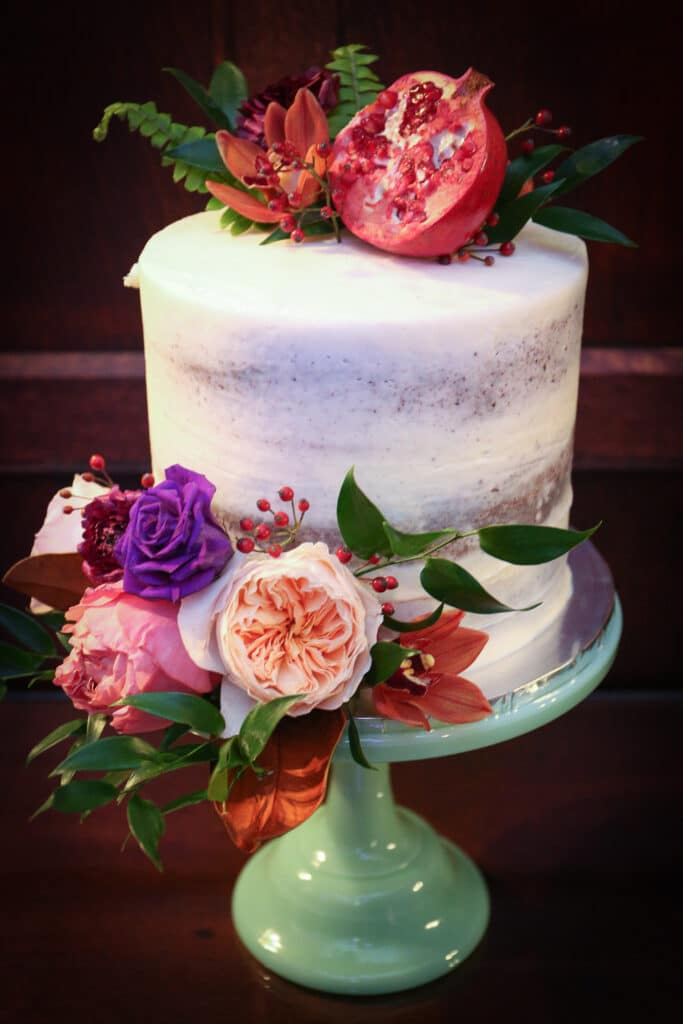 three-layer wedding cake decorated with fresh flowers and pomegranates on mint glass cake stand