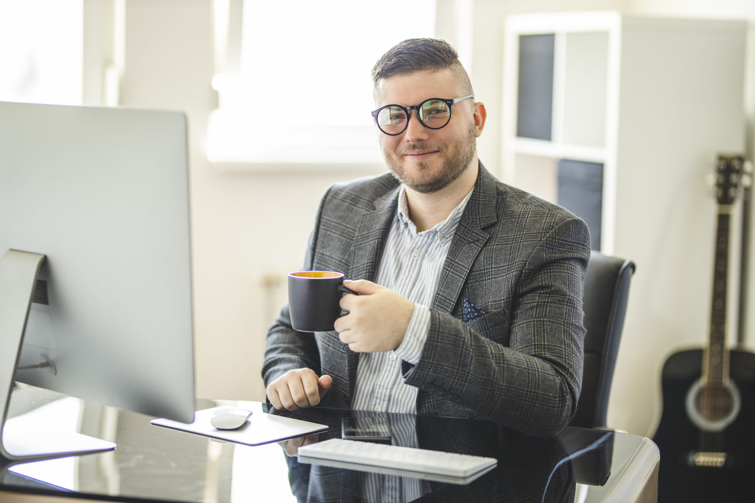 Portrait of successful entrepreneur drinking coffee and using computer at cozy home office