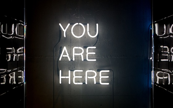 "Neon sign that reads ""you are here"""