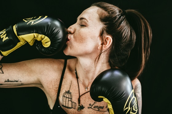 Woman wearing boxing gloves to do sport and looking powerful