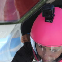 woman in pink skydiving helmet about to exit aircraft