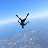 skydiver flies head down in front of St. John's River in Jacksonville FL