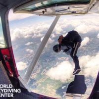 experienced skydiver perches on step outside of plane