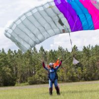 fun jumper lands with colorful canopy overhead