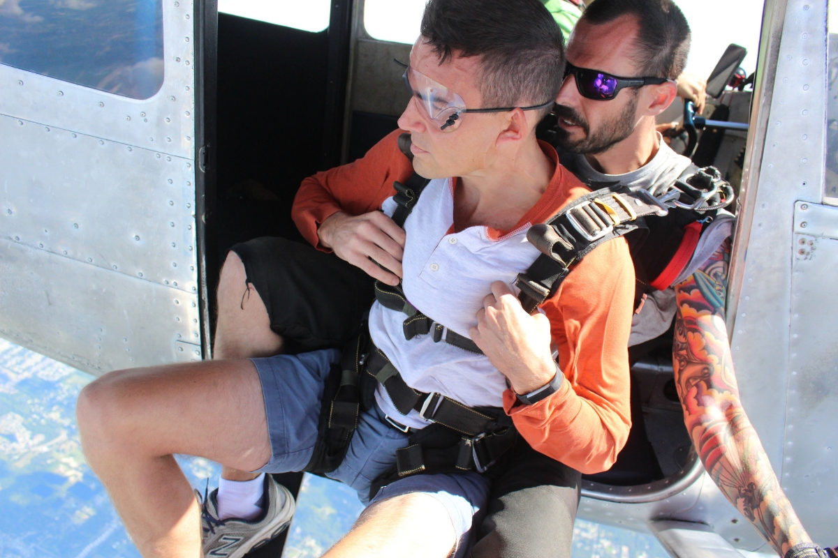 male tandem skydiving student sits at the edge of the plane before exiting