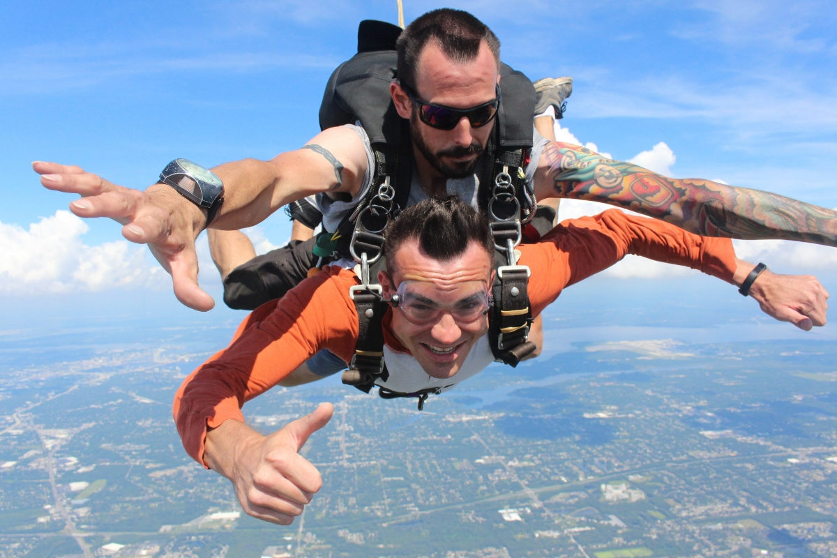 male tandem skydiving student gives thumbs up