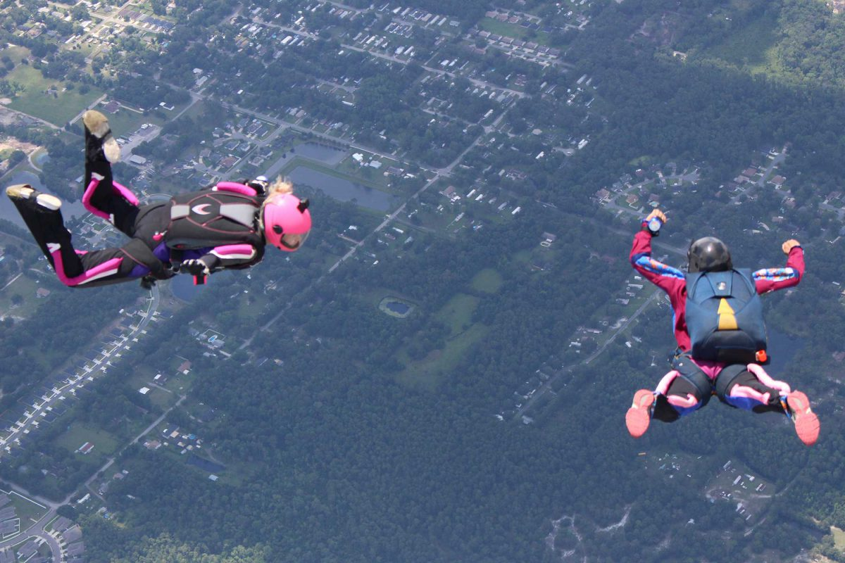 aff skydiving student in freefall while instructor looks on