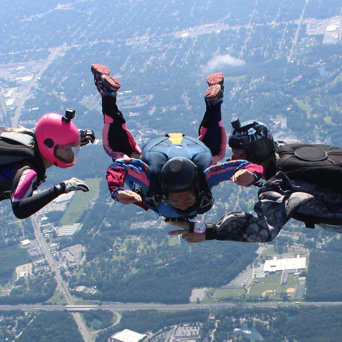 female learns to skydive with 2 instructors by her side