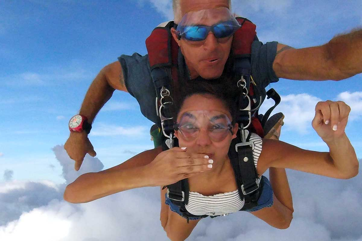 female blows kiss in the sky during tandem skydive