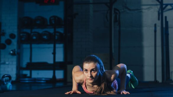 Women performing a burpee exercise in a dark backdrop