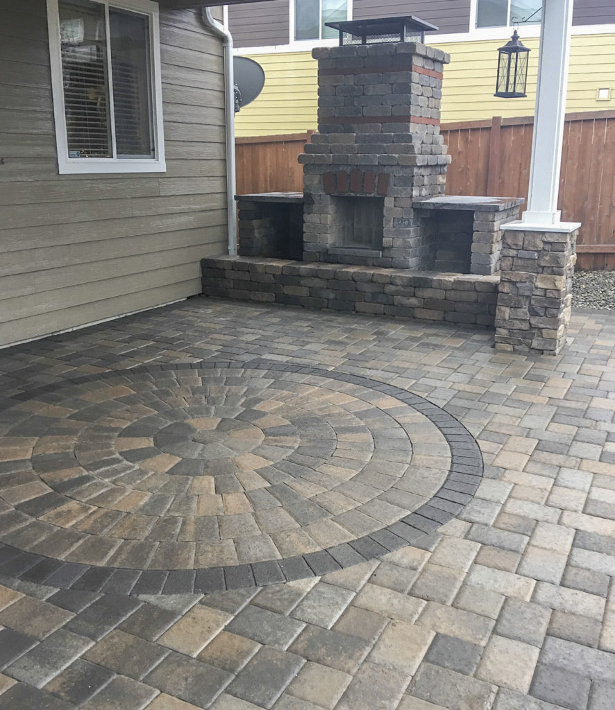 outdoor fireplace on paver patio with circle inset