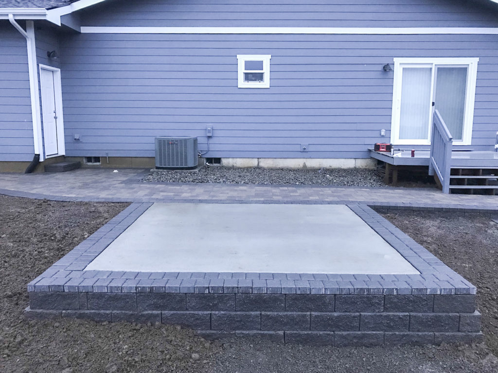 Hot tub pad with retaining wall