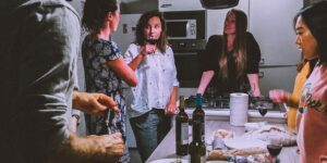A group of family and friends are standing around a kitchen counter, snacking, drinking wine, laughing, and talking together.