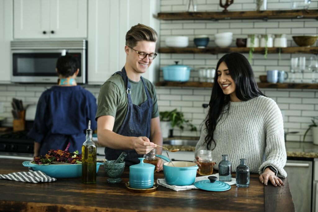 Three people are standing in a kitchen, cooking. One person has their back to the camera, two people face the camera. The people facing the camera are smiling and working with food on the counter.