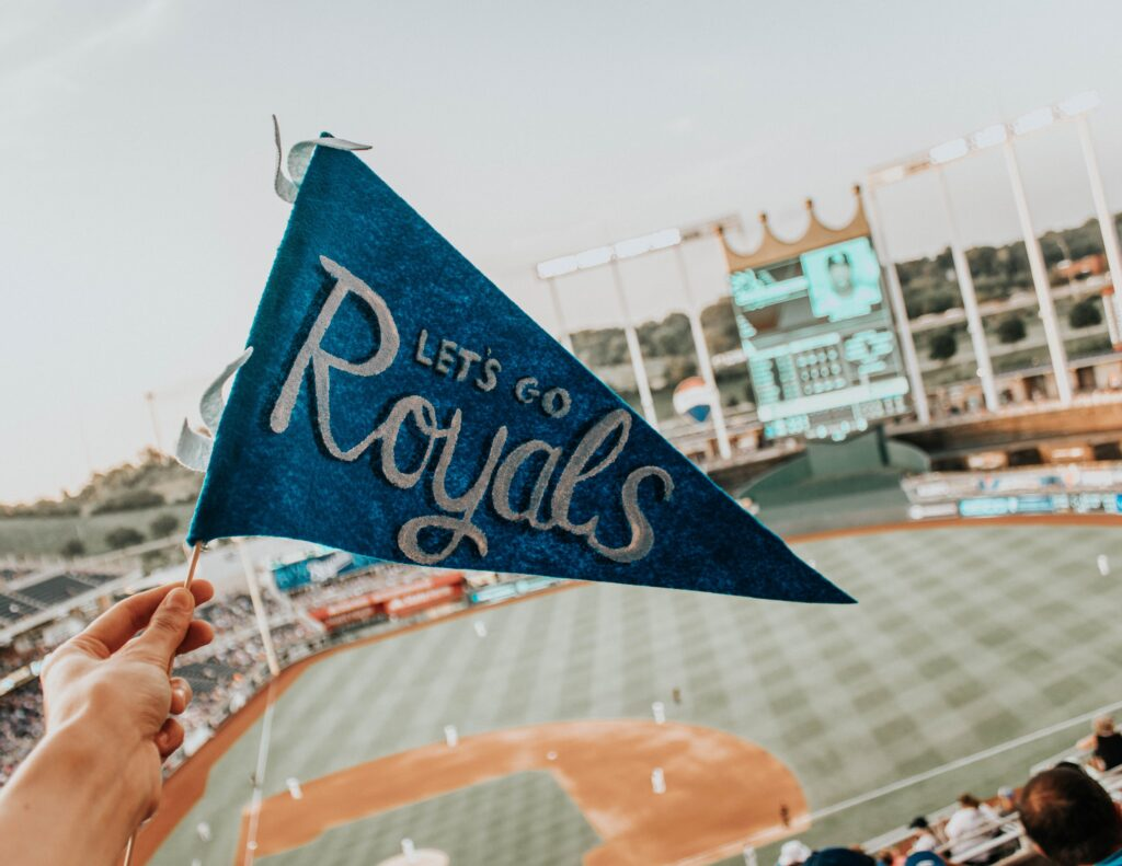 "A hand is holding up a small, blue flag reading ""Let's Go Royals"" against Kauffman Stadium (located in Kansas City, Missouri) as the background. On select days, people can bring their dogs to watch the Royals play!"