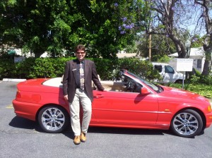Mike Perry standing with a convertible BMW