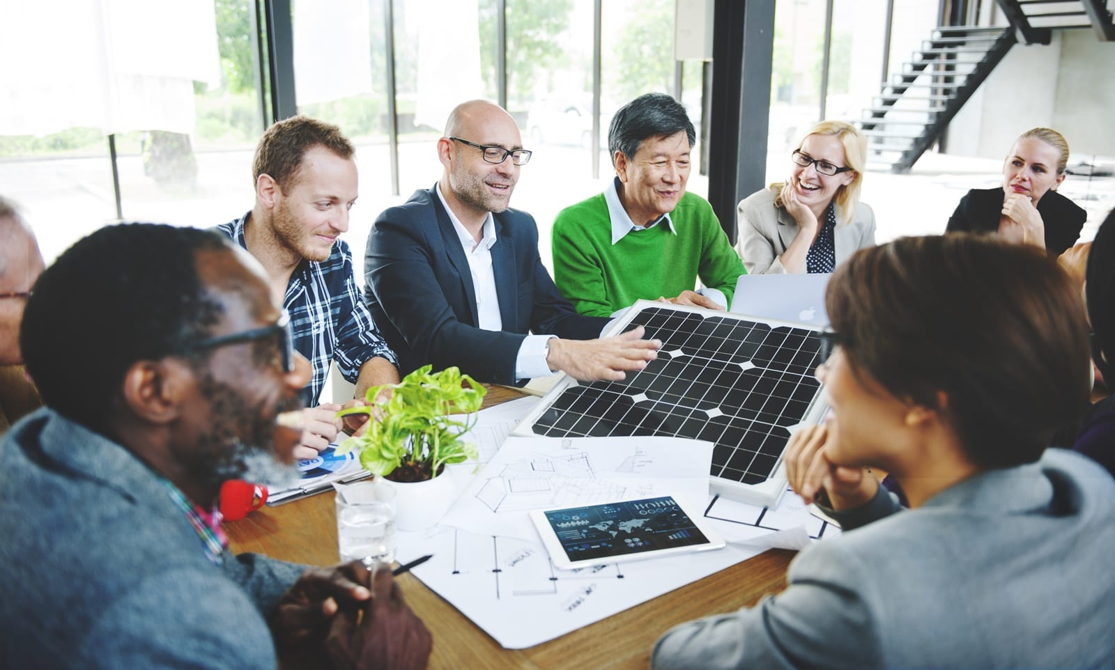 Group of diverse individuals sitting around conference table looking at a small solar pv module
