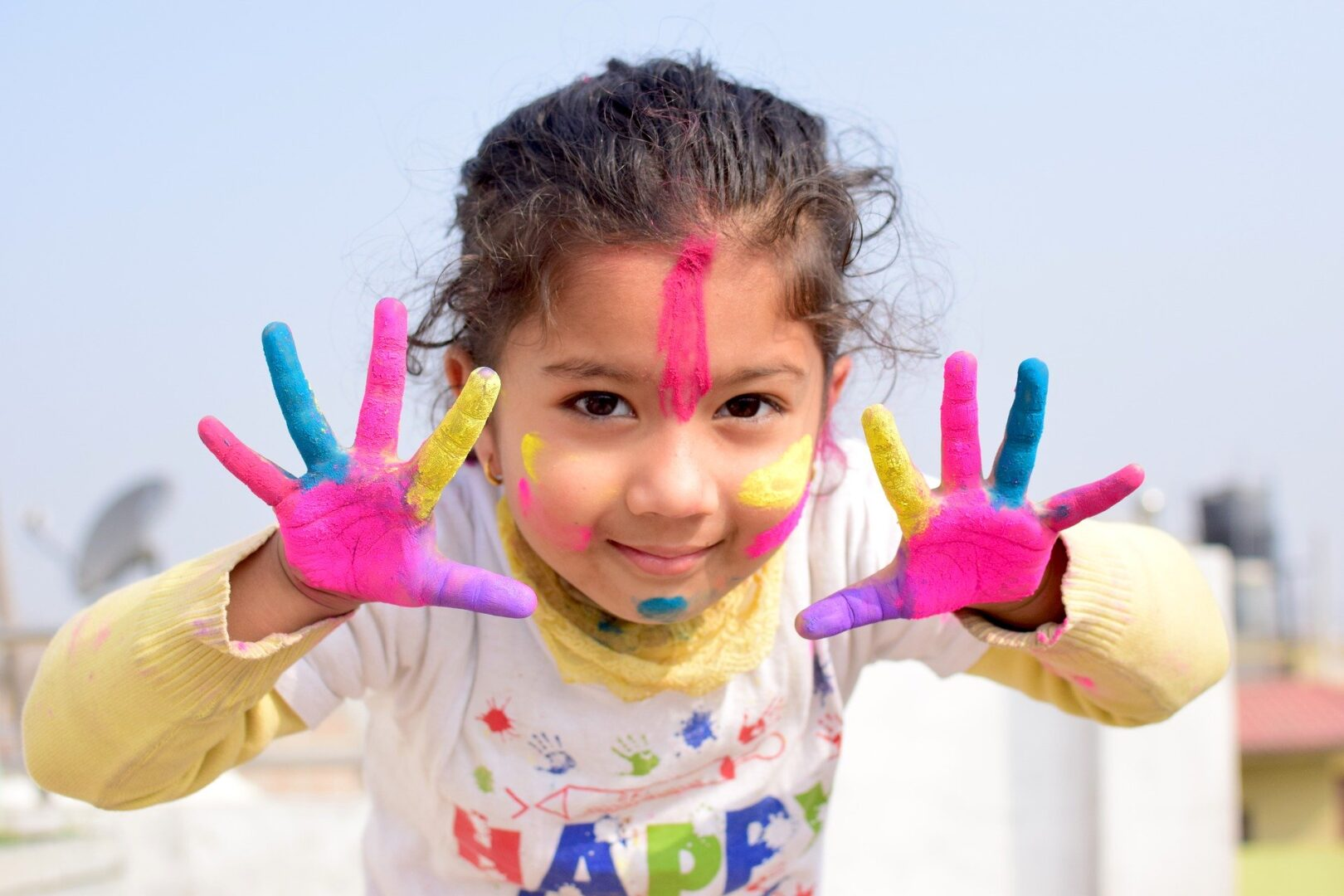 Child with paint on outspread fingers