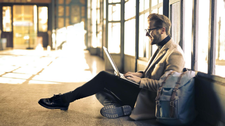 business casual person sits on floor using laptop and smiling