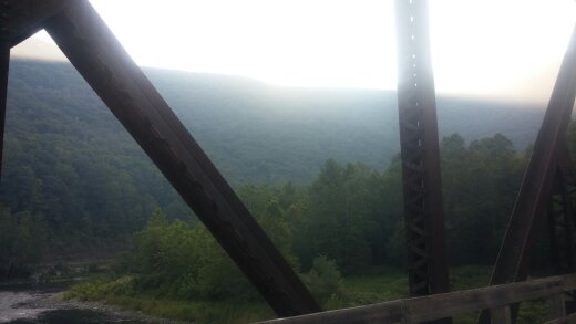 Sun coming up over the mountain as I cross a trestle bridge.