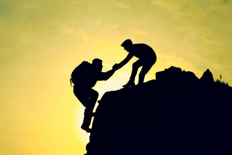 A man helping another up the mountain
