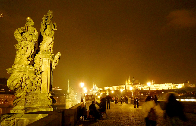 Charles Bridge lights up at night, while the Castle glows in the background.