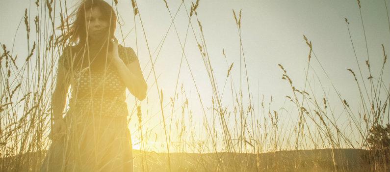 woman walking in tall grass