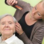 Caregiver grooming elderly woman