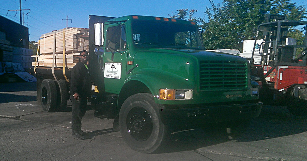 army green flatbed truck loaded for lumber delivery
