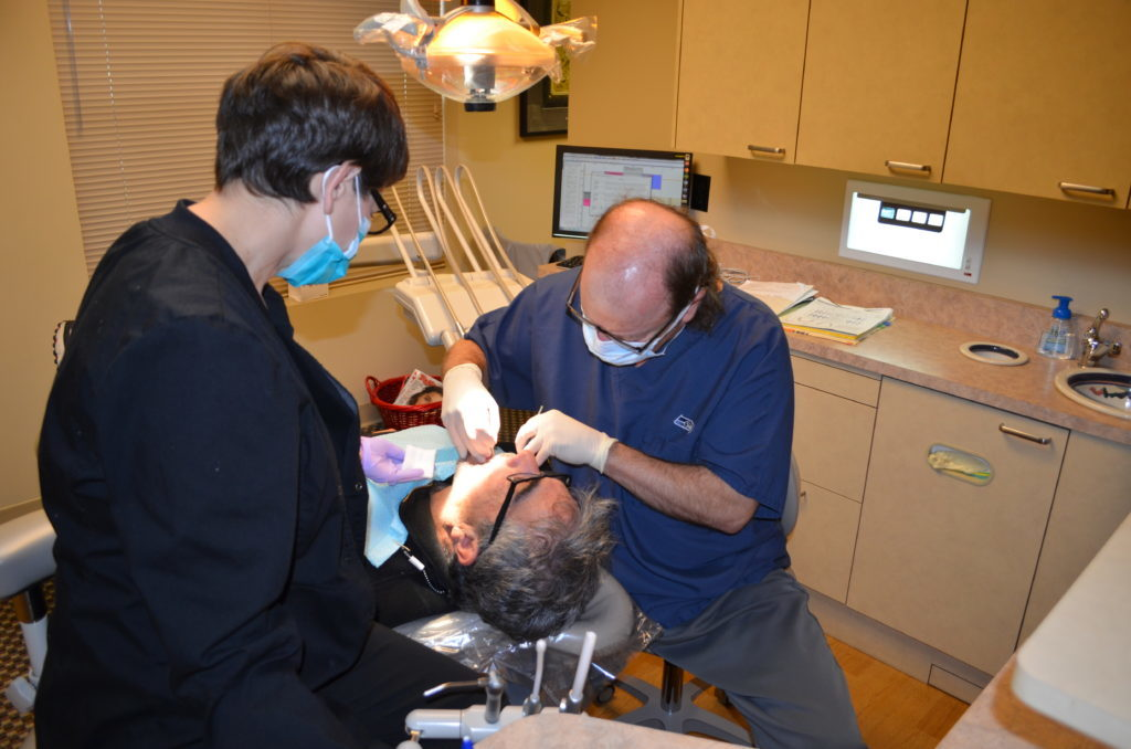 Dr. Hickey providing dental services to a patient in his Tacoma, WA office.
